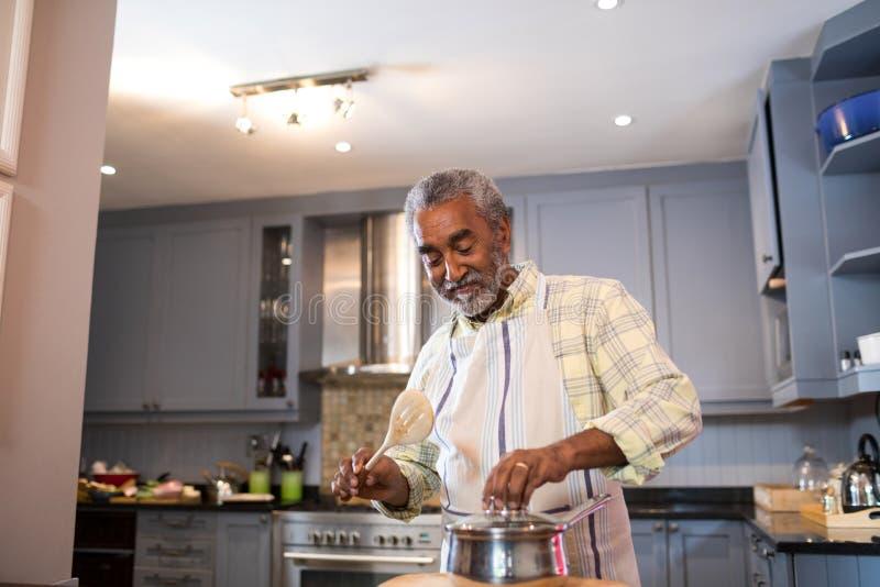 准备食物的老人在厨房里 免版税库存照片