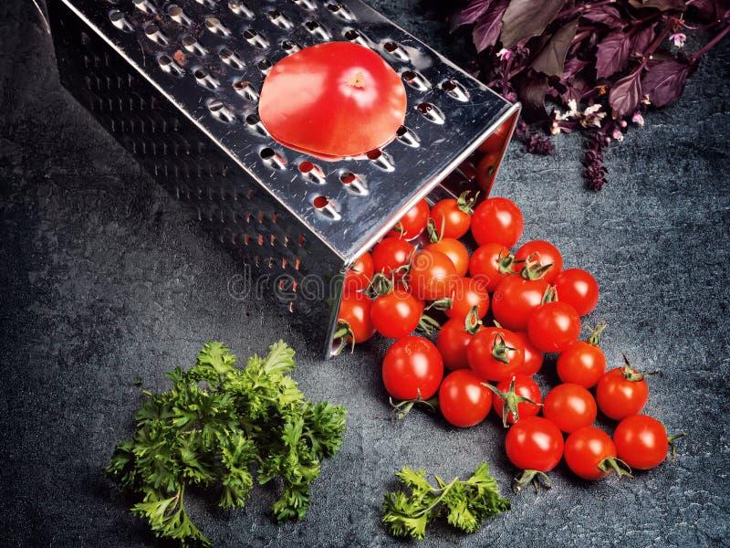 准备食谱西红柿汁 下来大蕃茄和老磨丝器对在减速火箭的葡萄酒土气灰色ston的小葡萄西红柿 库存图片