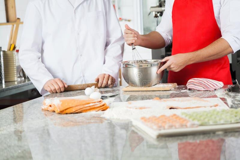 准备馄饨面团的男性厨师在柜台 免版税库存图片