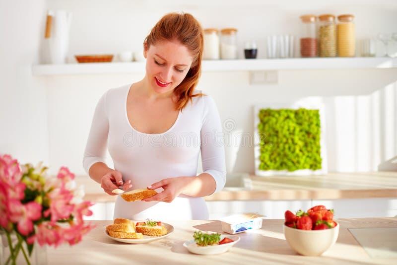 准备鲜美快餐的愉快的少妇在早晨光的厨房用桌上 库存图片