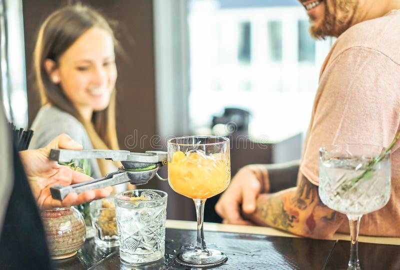 准备鸡尾酒的侍酒者倾吐石灰-等待饮料的愉快的朋友在美国酒吧的柜台 图库摄影
