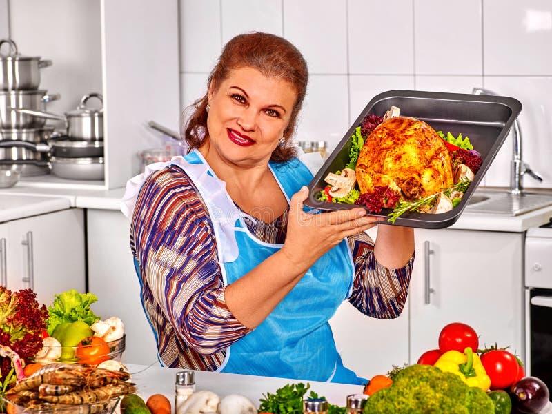 准备鸡的成熟妇女在厨房 免版税库存照片