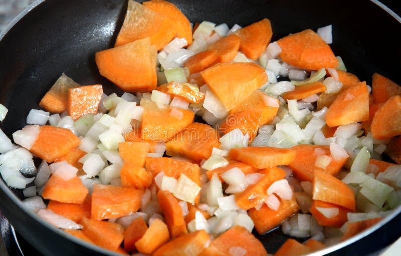 准备:红萝卜和葱在煎锅 免版税图库摄影