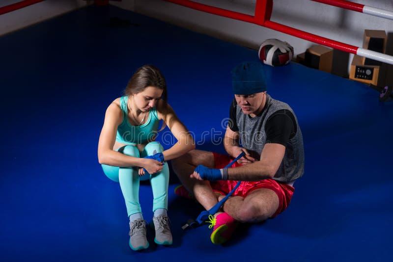 准备绷带的男性运动的拳击手坐在运动femal附近 免版税库存照片