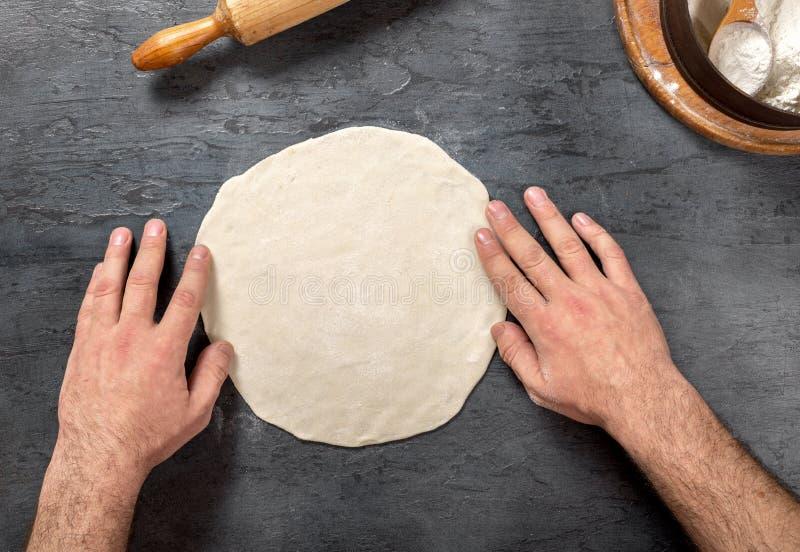 准备黑暗的石表面上的男性手薄饼面团 库存图片