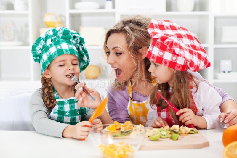 准备水果沙拉的妇女和小女孩 免版税图库摄影