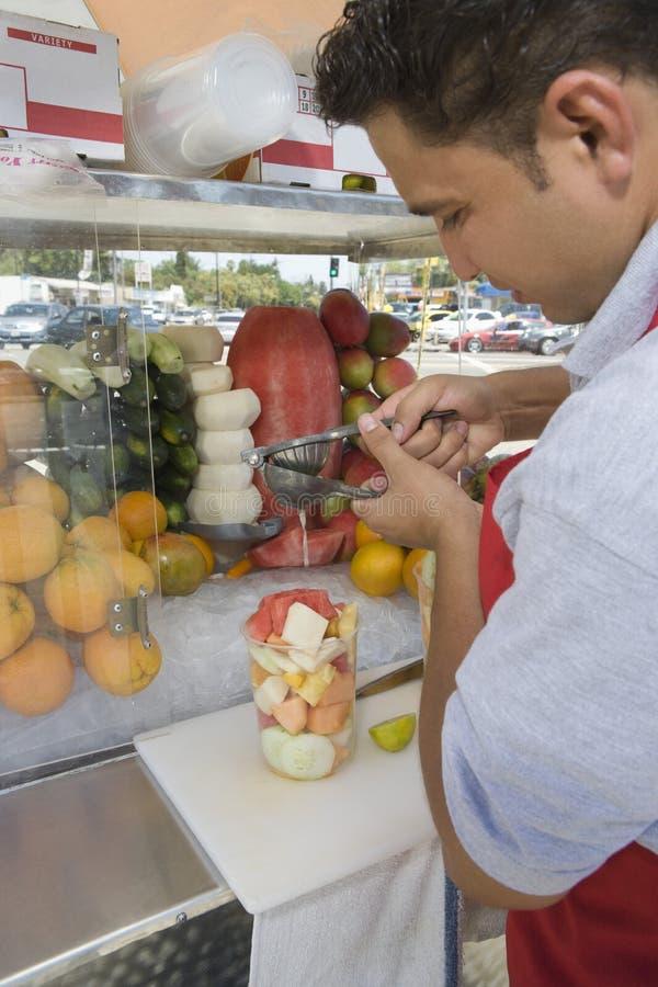 准备水果沙拉的摊贩 库存图片