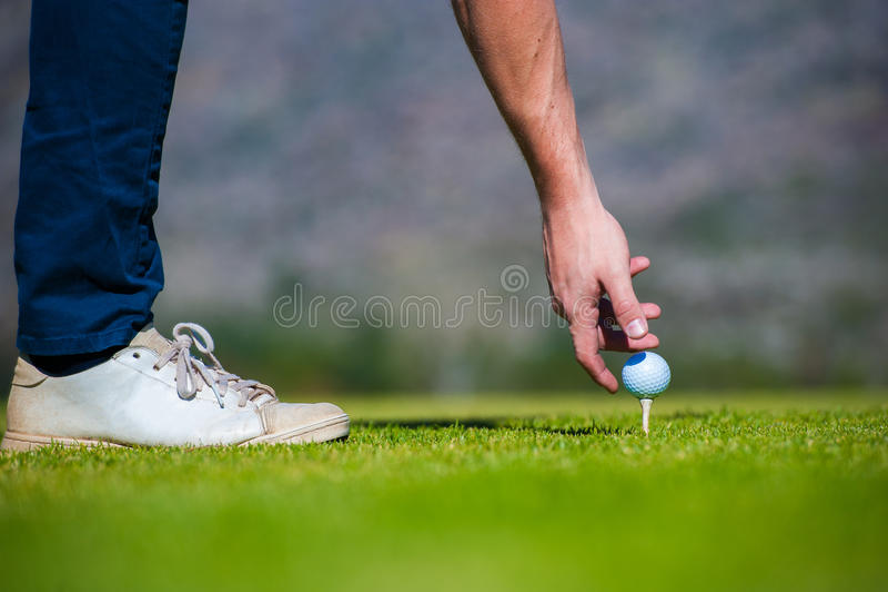 准备从高尔夫球发球区域的观点的高尔夫球运动员 免版税库存图片