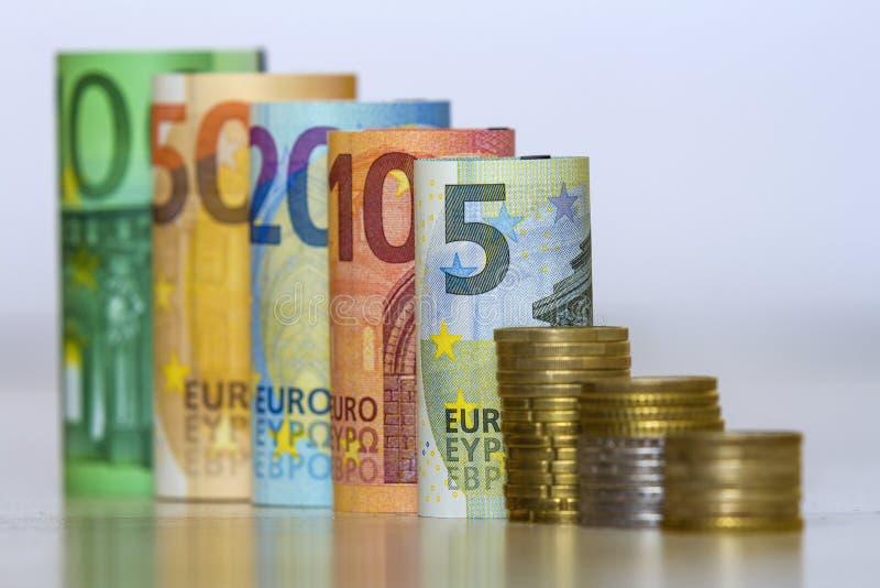 准确地滚动的一百,五十张,二十张,十张和五张新的纸欧洲钞票和堆平直的行金属硬币孤立 免版税库存图片