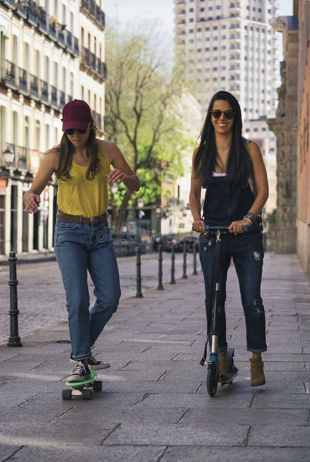 凉快的女孩夫妇乘坐的滑行车和冰鞋,现代友谊概念 免版税库存照片