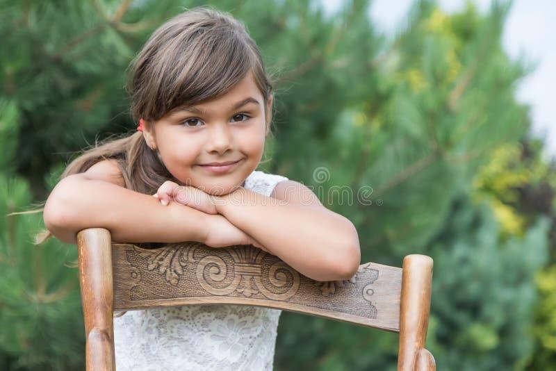 凉快的小女孩在葡萄酒木椅子倾斜 库存照片