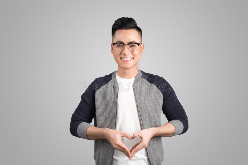 凉快的英俊的亚裔人画象用做心脏shap的手 库存图片