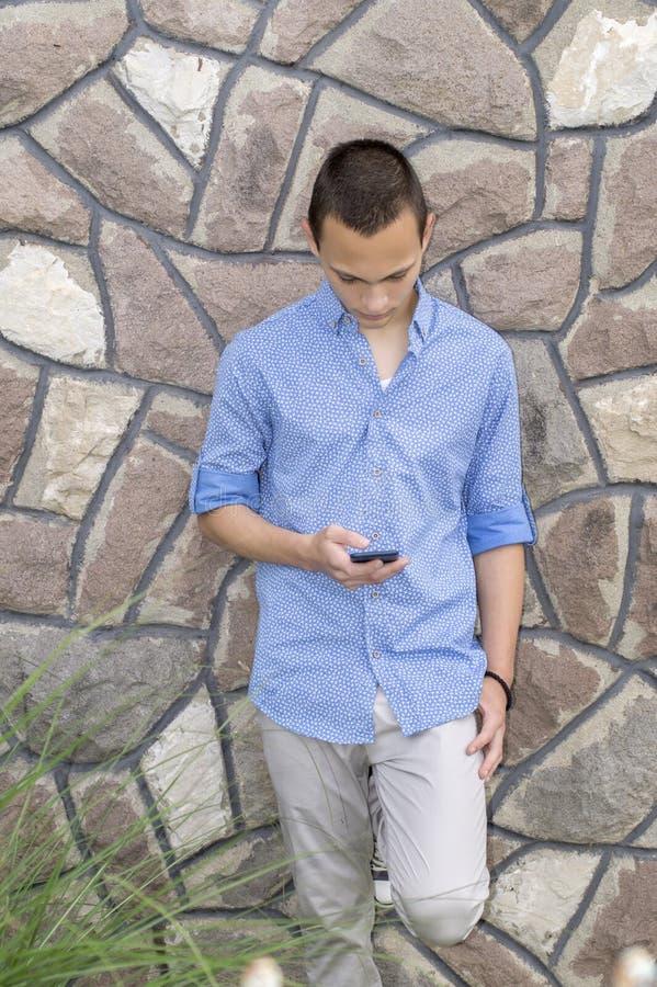 凉快的年轻人读书正文消息画象在他的cellphon的 免版税库存照片