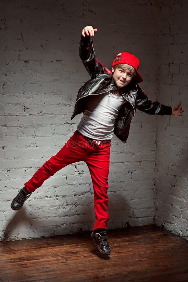 凉快的年轻Hip Hop男孩画象白色衬衣和黑皮夹克的在顶楼 免版税库存照片
