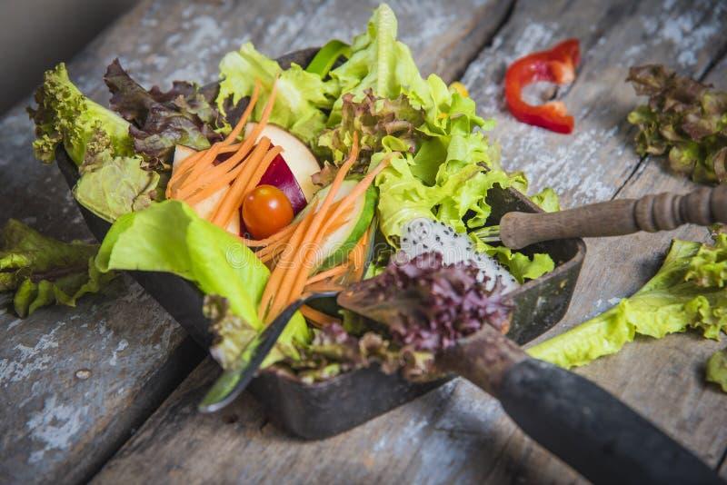凉拌生菜选择聚焦在方形的平底锅的在木表上 免版税库存图片