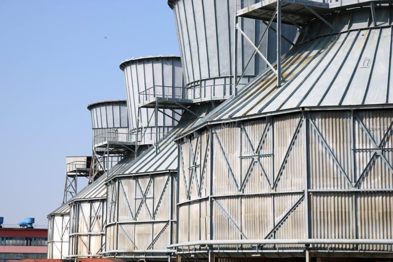 凉水的大灰色冷却塔在炼油厂连续站立,动力设备,石油化学制品,化学制品 免版税库存照片