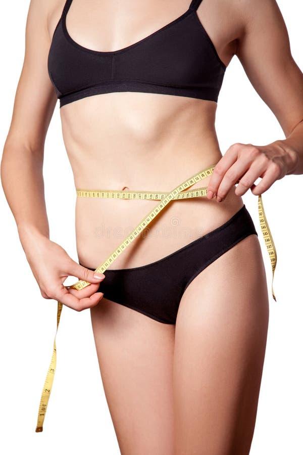 减肥有措施卷尺的适合的愉快的少妇她的有黑内衣的腰部,隔绝在白色背景 免版税库存照片