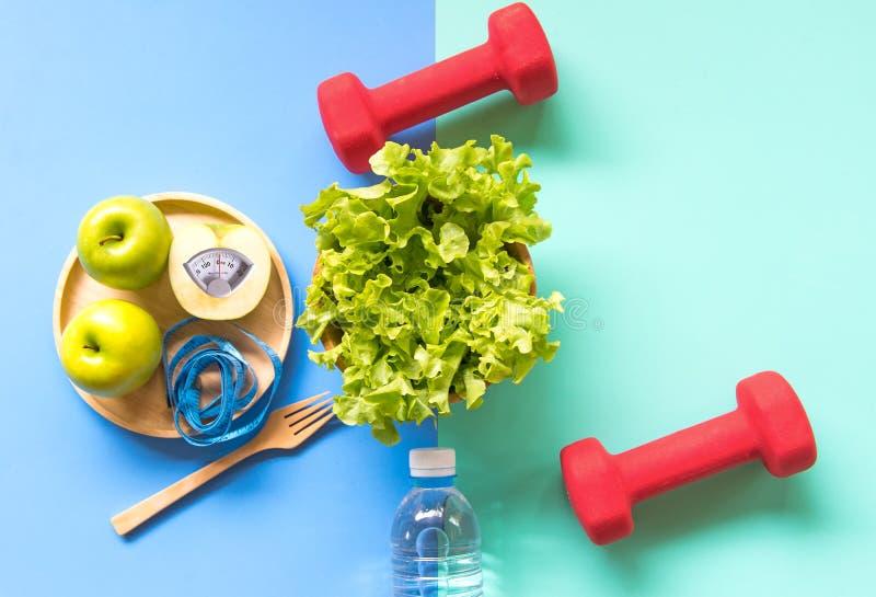 减肥重量用绿色苹果和测量轻拍,在木板材的标度重量,菜,哑铃,五颜六色的backgrou的饮食 免版税库存图片