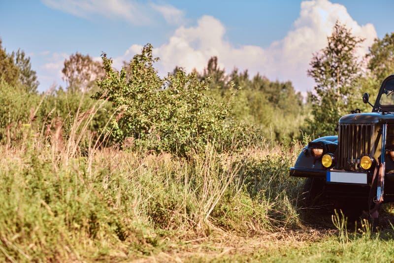 减速火箭的军用汽车在干草原森林里在晴天 免版税库存照片