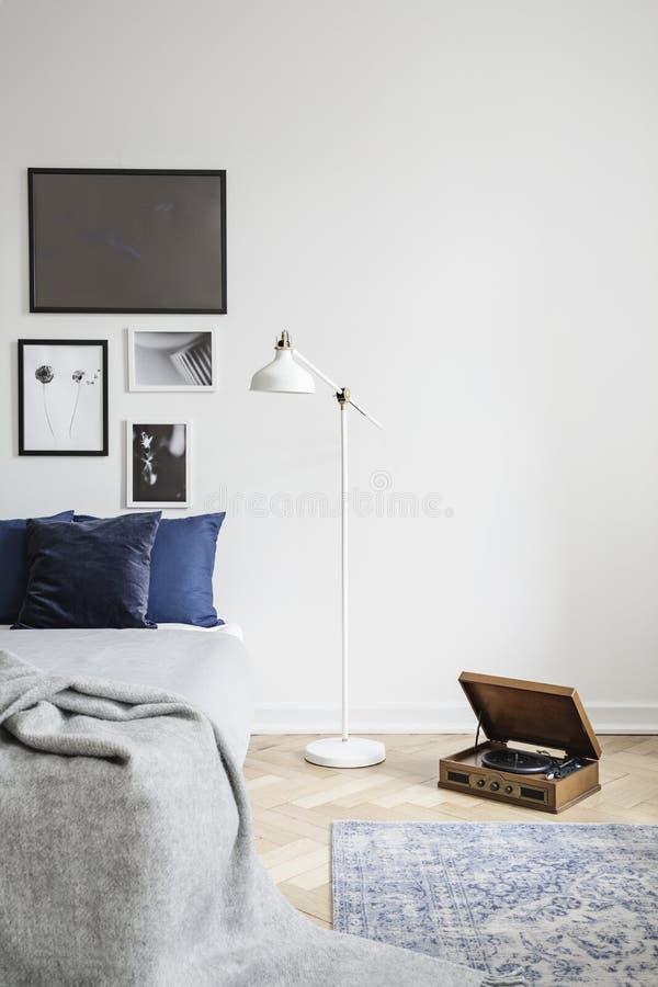减速火箭的唱片球员和一盏工业样式落地灯在有被构筑的图片的一间行家卧室 库存照片