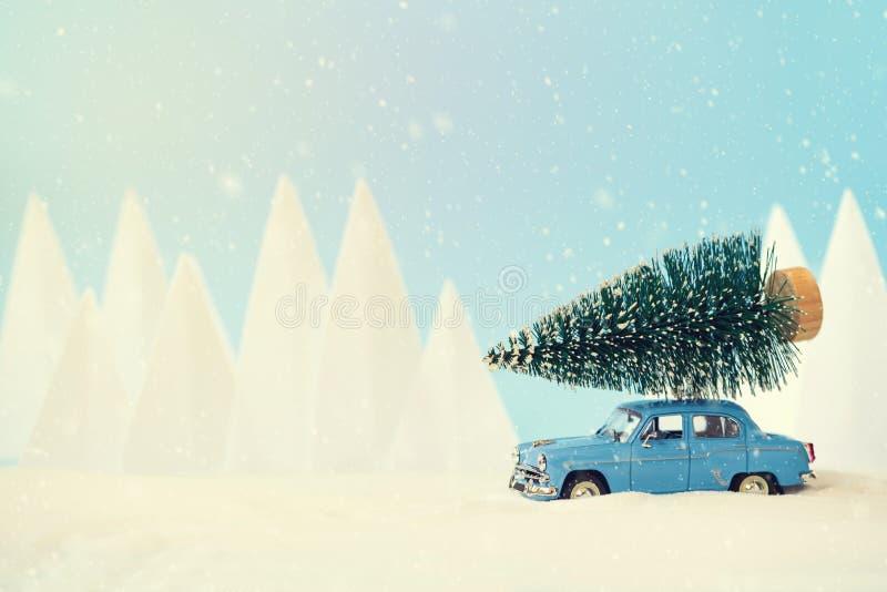 减速火箭的在多雪的风景的汽车玩具运载的圣诞节杉树 圣诞节或新年庆祝概念 r r 免版税库存图片