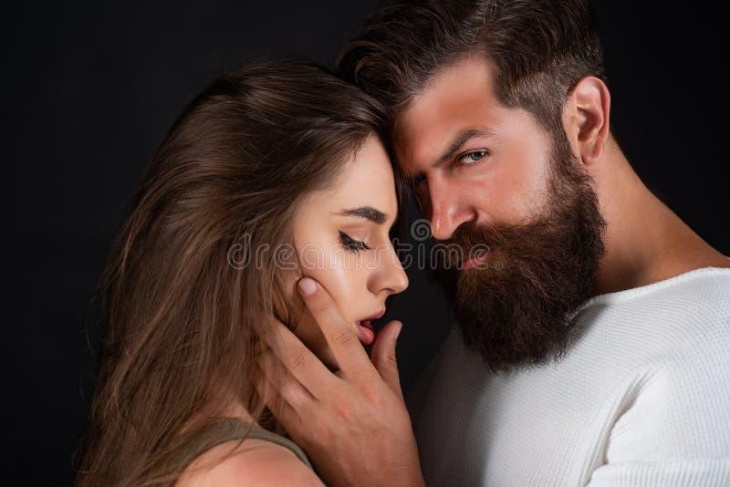 ?? 减速火箭的夫妇 诱惑他可爱的女朋友的英俊的年轻人 亲吻美好的年轻的夫妇和 图库摄影