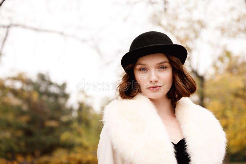 减速火箭的女孩画象黑帽会议的,皮大衣和黑手套在秋天停放 免版税图库摄影