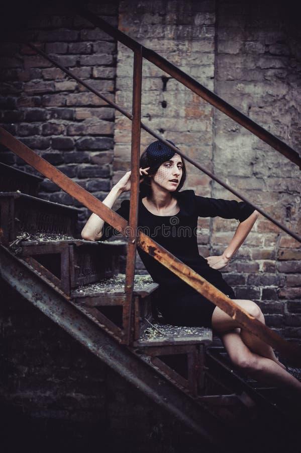 减速火箭的妇女纵向 葡萄酒样式女孩佩带的古板的帽子 浪漫夫人坐葡萄酒伪造了楼梯 有选择性的f 免版税库存照片