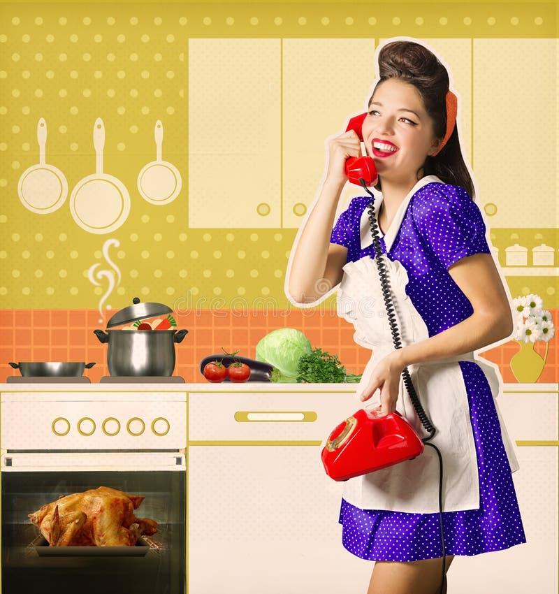 减速火箭的妇女谈话在电话和厨师烤在她的l chiicken 图库摄影