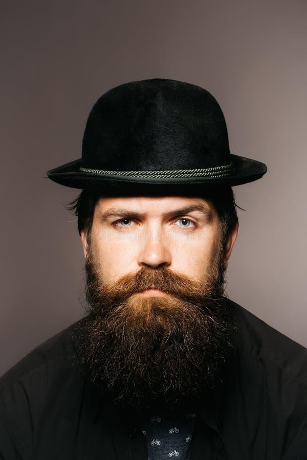 黑减速火箭的帽子的有胡子的绅士 免版税库存图片