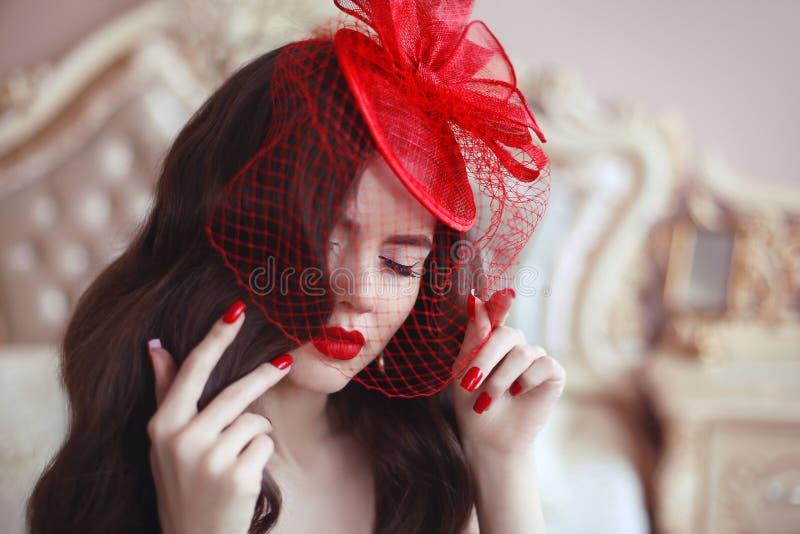 减速火箭的帽子的端庄的妇女有红色嘴唇和被修剪的钉子的 增殖比 库存照片
