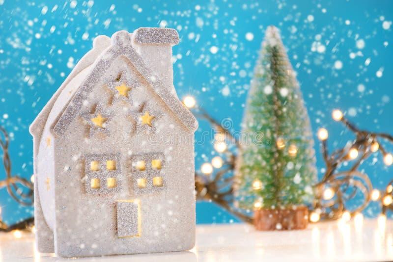 减速火箭的房子玩具在与雪剥落和圣诞树的冬日在背景中 免版税库存照片