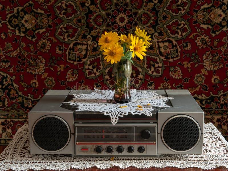 减速火箭的收音机和音乐播放器在一张木桌上与一个花瓶花 库存图片