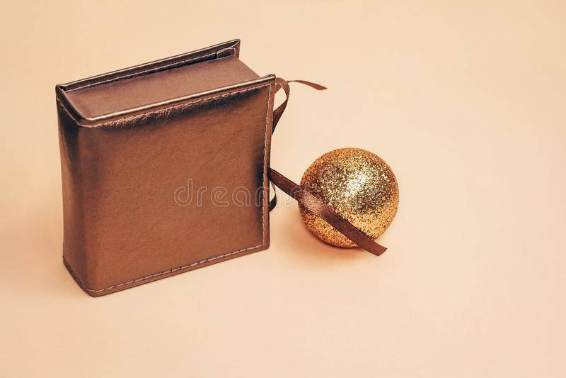 减速火箭的有单独一把丝绸弓的样式古铜色的当前箱子与在淡色背景的金子闪耀的圣诞节球 库存照片