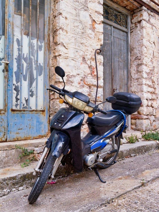 减速火箭的样式小型摩托车老希腊石议院外 免版税图库摄影