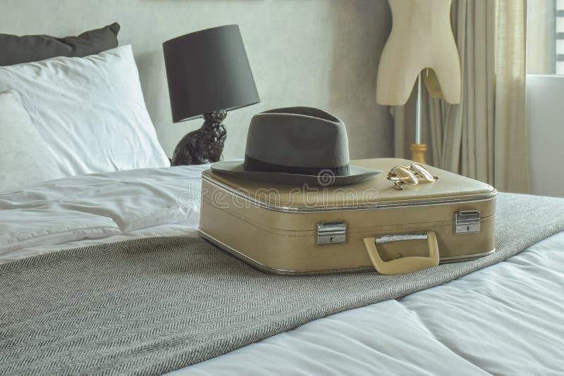 减速火箭的样式旅行袋子、帽子和太阳镜在床上在旅馆客人 免版税图库摄影