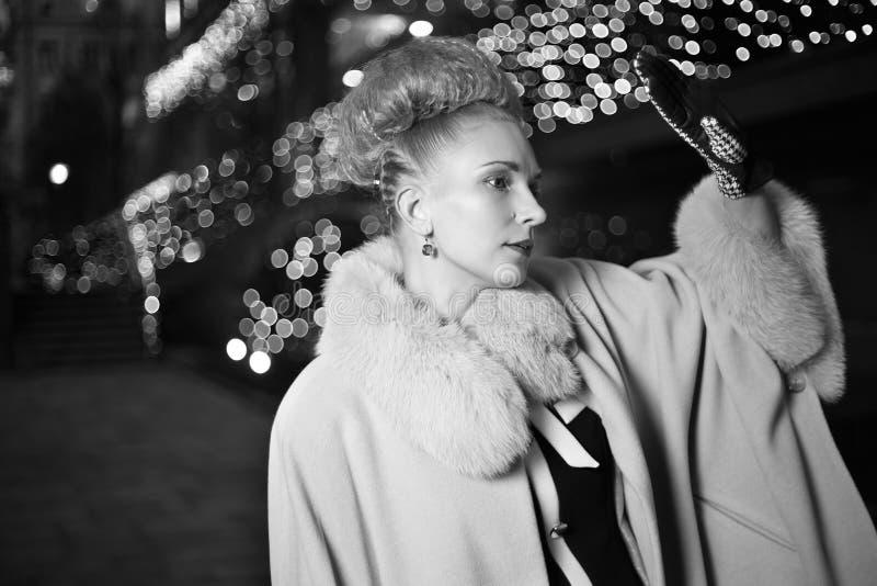 减速火箭的样式的典雅的白肤金发的妇女在平衡的秋天户外 库存照片