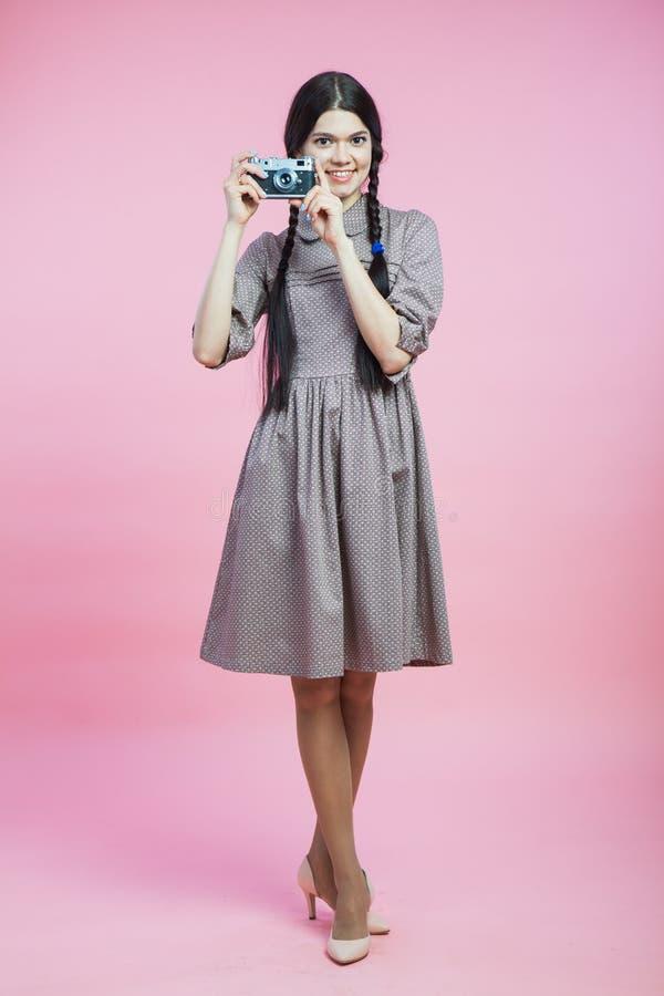 减速火箭的样式礼服的美丽的小姐有葡萄酒照片照相机的 库存照片