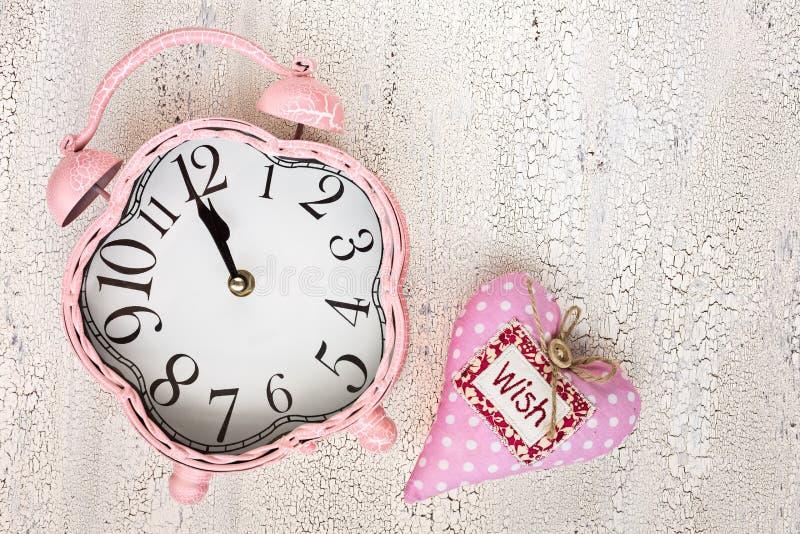 减速火箭的桃红色时钟和软的桃红色心脏与词祝愿在木ba 免版税库存图片