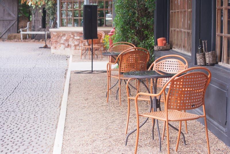 减速火箭的椅子和桌在走道旁边的餐馆在室外 免版税图库摄影