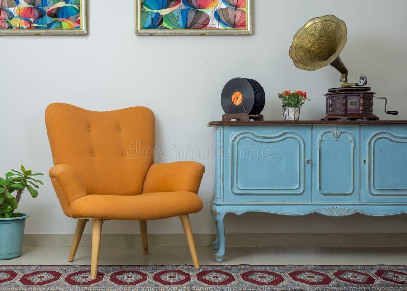 减速火箭的橙色扶手椅子、葡萄酒木浅兰的餐具柜、老留声机留声机、唱片和有启发性台灯 库存图片