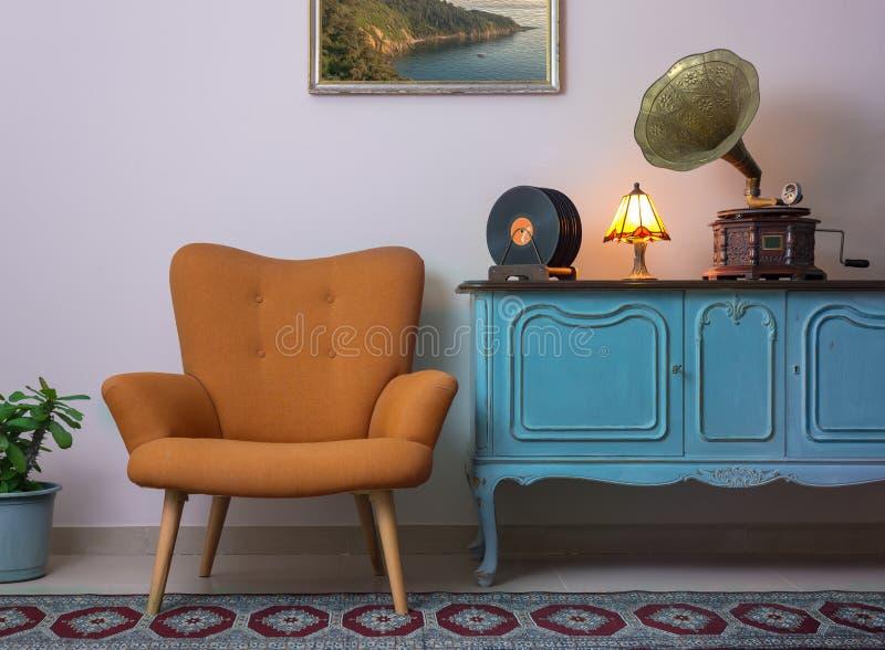 减速火箭的橙色扶手椅子、葡萄酒木浅兰的餐具柜、老留声机留声机和唱片葡萄酒内部  免版税库存图片