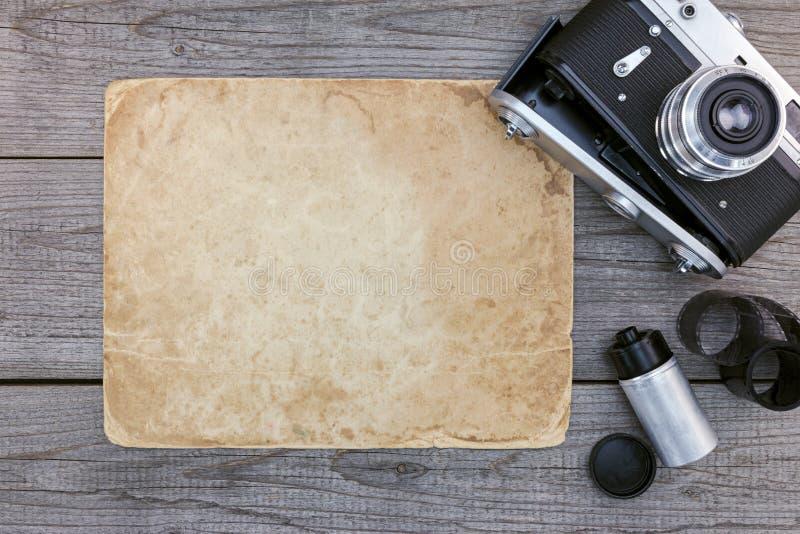 减速火箭的照相机、底片和老包装纸在灰色木t 免版税库存照片