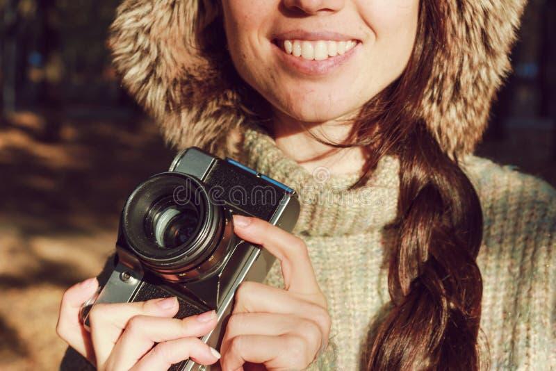 减速火箭的照相机在手中年轻摄影师女孩和准备好拍照片 免版税库存照片