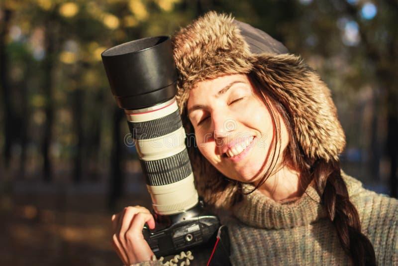 减速火箭的照相机在手中年轻摄影师女孩和准备好拍照片 免版税图库摄影
