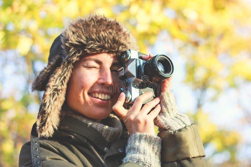 减速火箭的照相机在手中年轻摄影师女孩和准备好拍照片 免版税库存图片