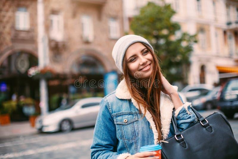减速火箭的牛仔裤的时髦的行家女孩适合并且编织了帽子摆在她拿着咖啡去的街道的,微笑友好 库存照片