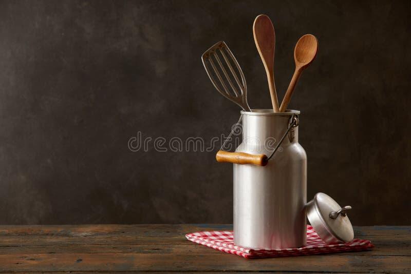 减速火箭的牛奶能与在木桌上的厨具 图库摄影