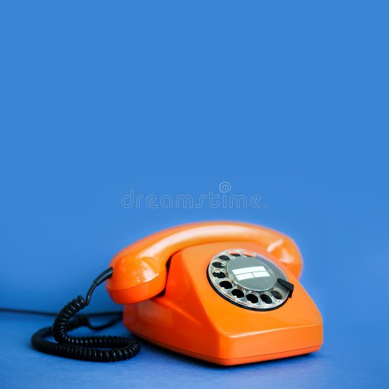 减速火箭的电话橙色颜色,葡萄酒排字了在蓝色背景的接收器 浅深度领域摄影,拷贝空间 免版税库存照片