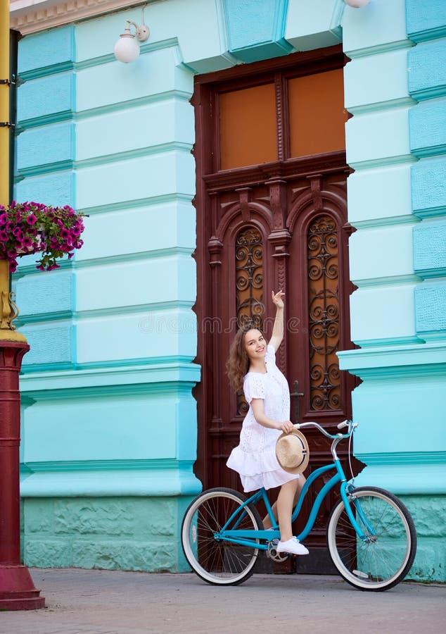 减速火箭的自行车的俏丽的女孩反对葡萄酒门在夏天 免版税库存图片
